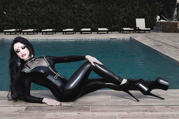 Ausrie Fel models her studded latex catsuit with fishnet insert